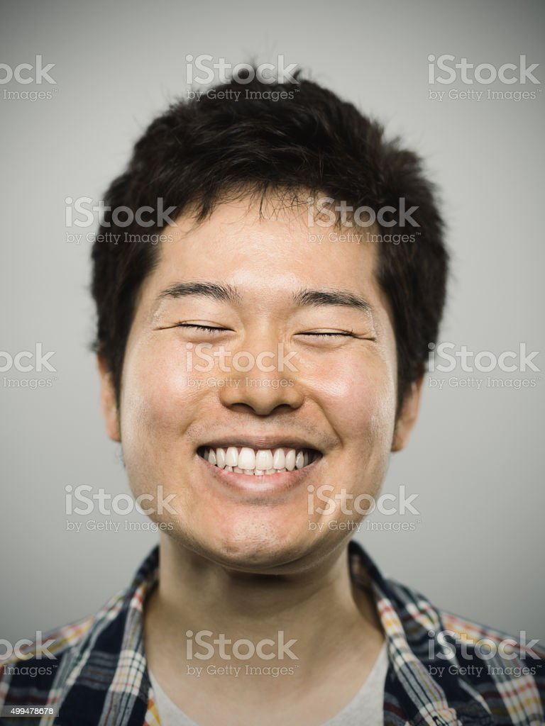 Portrait of a young happy japanese man looking at camera stock photo