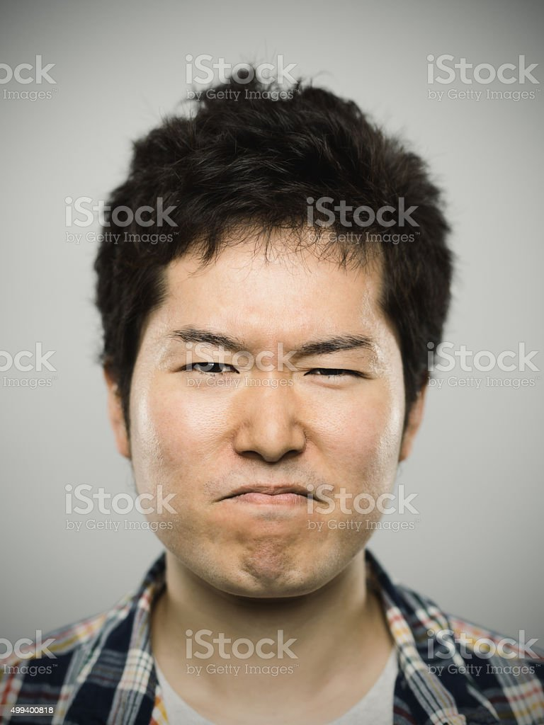 Portrait of a young japanese angry man looking at camera stock photo