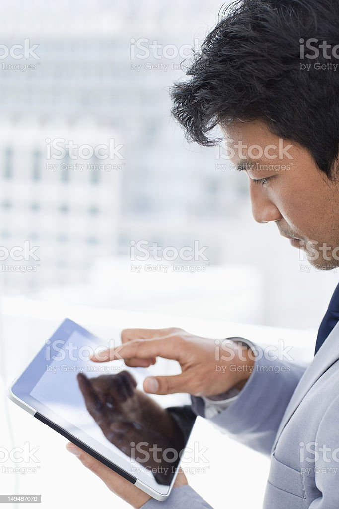 Portrait of a young office worker using his tablet computer royalty-free stock photo