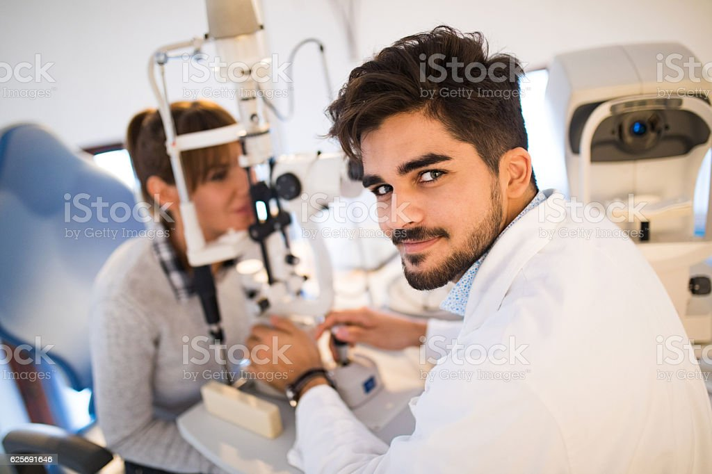 Portrait of a young optometrist with a female patient stock photo
