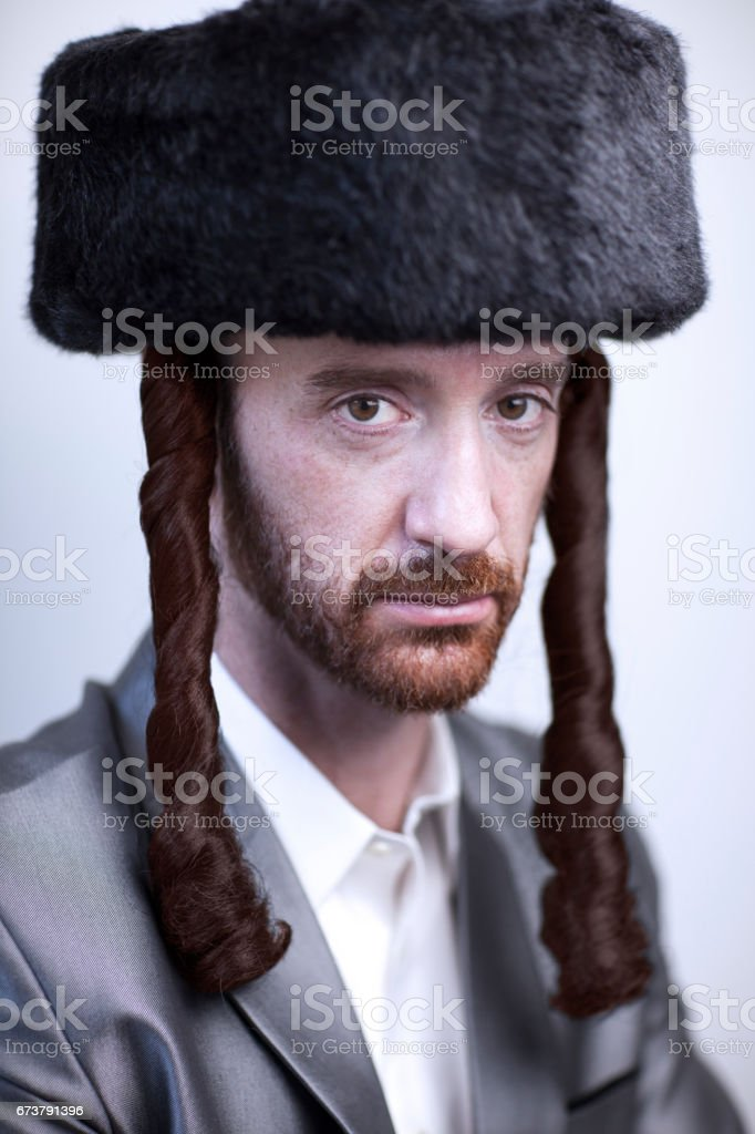 Portrait of a young orthodox Hasdim Jewish man with red beard and black fur hat in a silver business suit stock photo