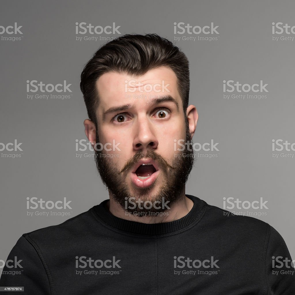 Portrait of a young puzzled businessman with opened mouth stock photo