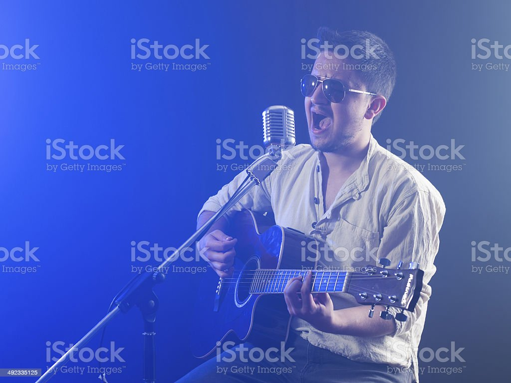 Portrait of a young singer playing acoustic guitar in smoke royalty-free stock photo