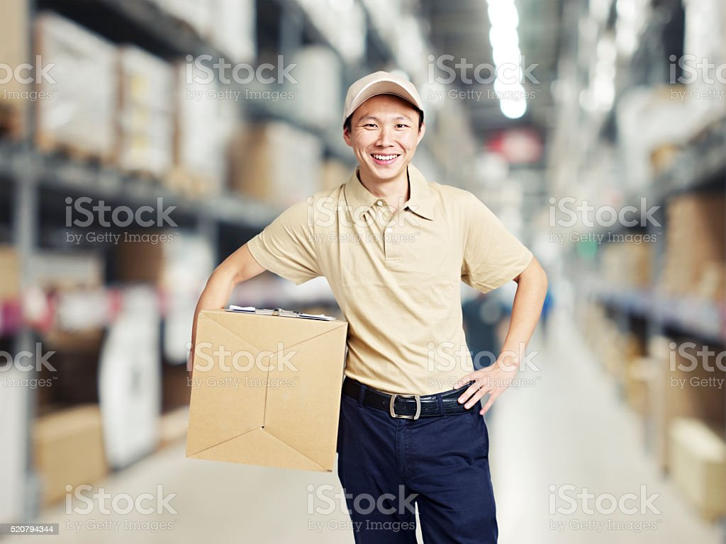 portrait of a young warehouse worker carrying a carton box stock photo