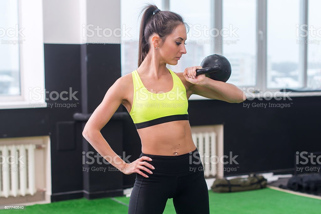 portrait of a young woman doing dumbbell lifting in gym stock photo