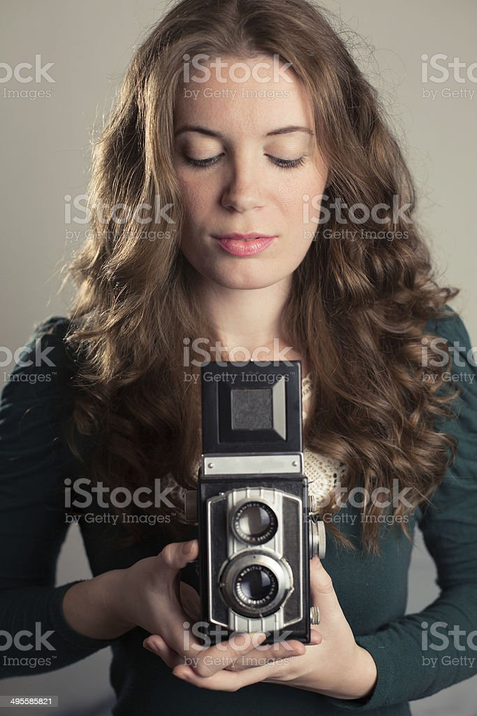 Portrait of a young woman holding a vintage camera stock photo