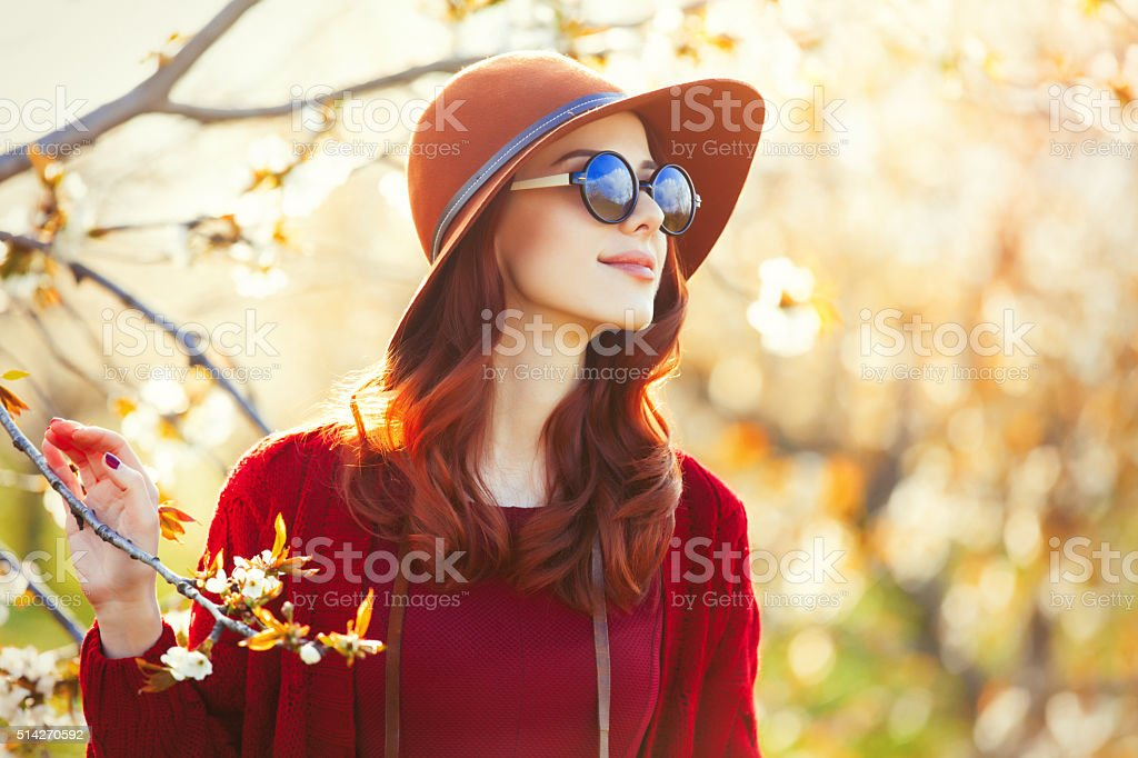 portrait of a young woman near blooming tree stock photo