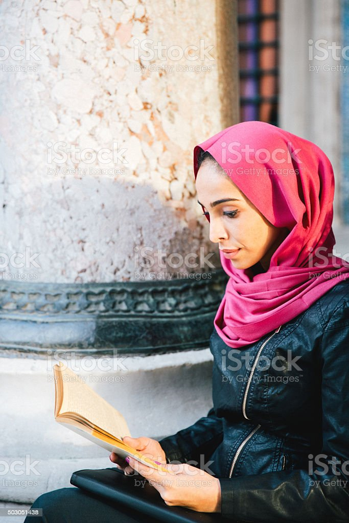 Portrait Of A Young Woman Reading A Book Outdoors stock photo