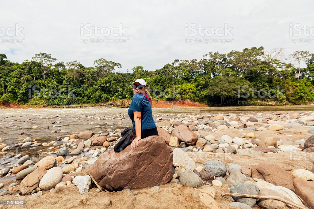 Portrait Of A Young Woman Sitting On A Rock stock photo