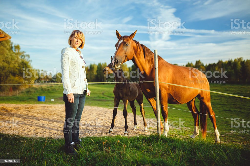 Portrait of a young woman standing posing with horses stock photo