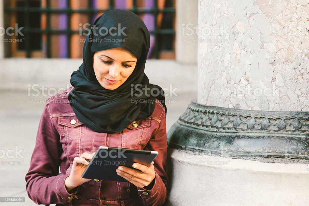 Portrait Of A Young Woman Wearing Headscarf Using Tablet Outdoors stock photo
