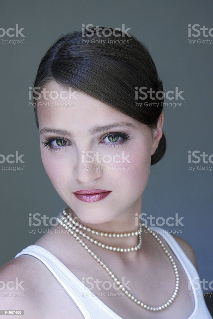 Portrait of a young woman wearing pearls, gray, white royalty-free stock photo