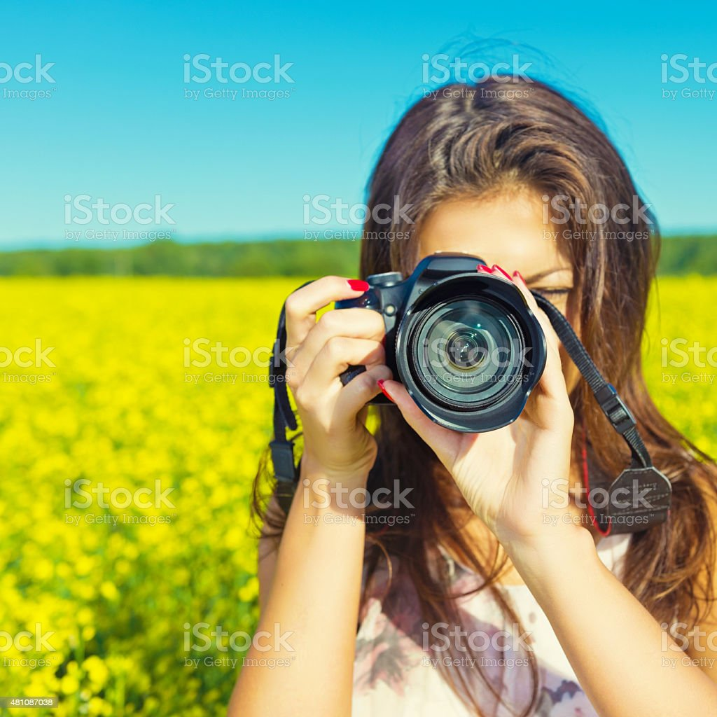 Portrait of a young woman with a camera outdoors stock photo