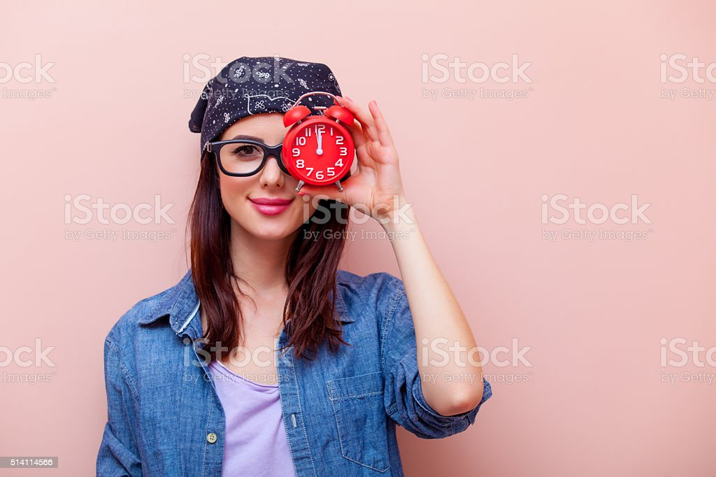 portrait of a young woman with alarm clock stock photo