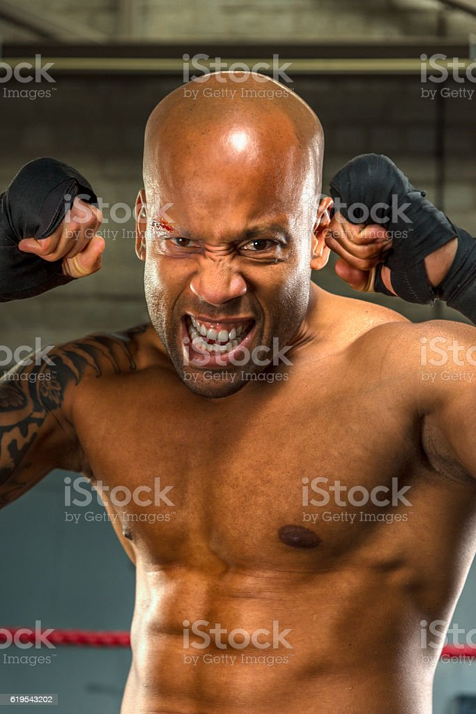 Portrait of aaggressive and wounded boxer  in boxing gym stock photo