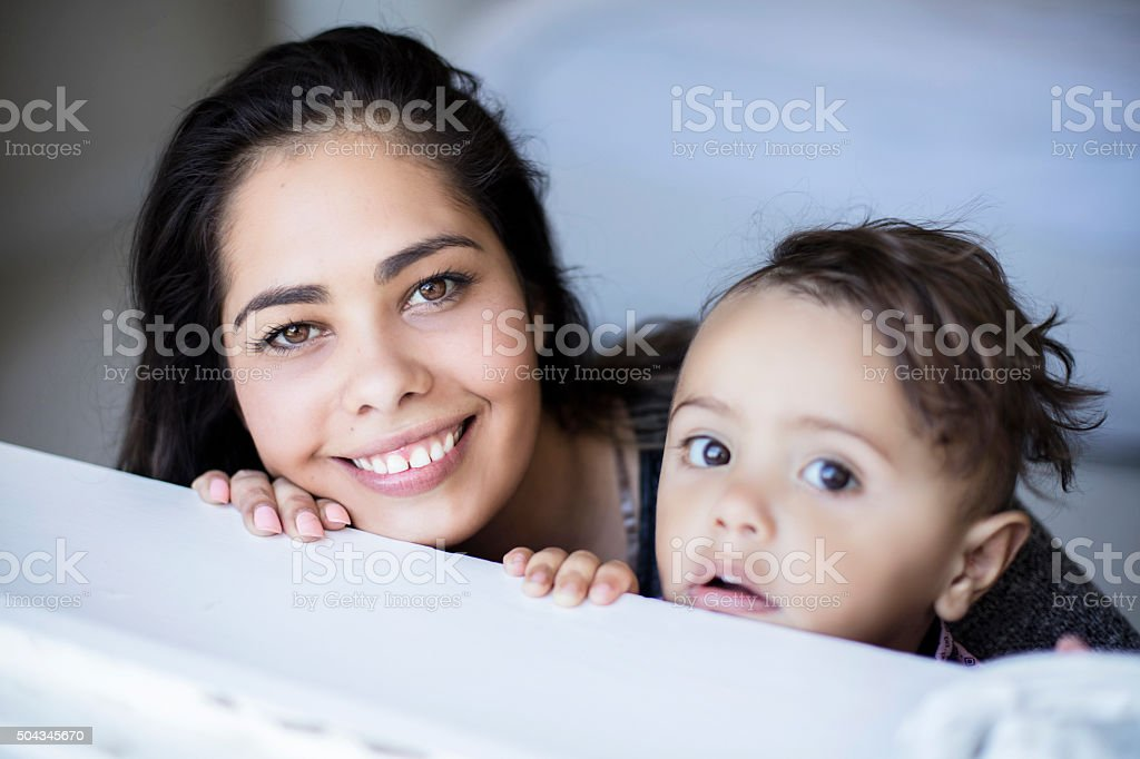 Portrait of Aboriginal mother and son looking to the window stock photo