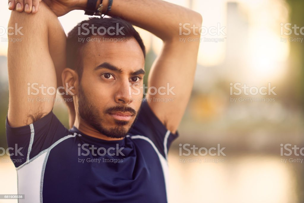 Portrait of active millenial man jogging at dusk with an urban cityscape and sunset in the background stock photo