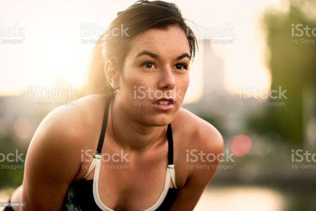 Portrait of active millenial woman jogging at dusk with an urban cityscape and sunset in the background stock photo