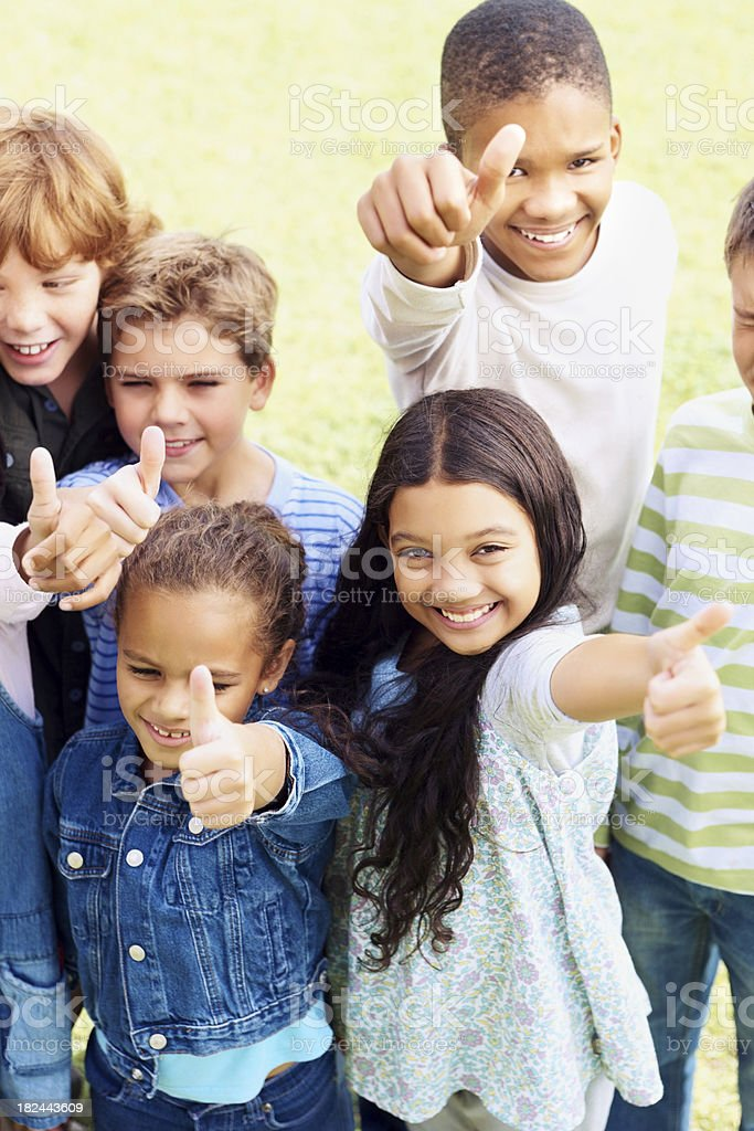 Portrait of adorable children showing a thumbs up sign royalty-free stock photo