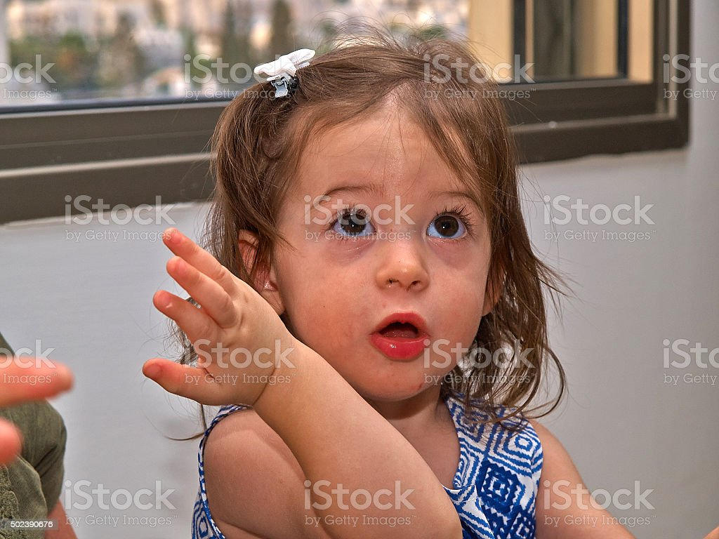 Portrait of adorable confused toddler girl stock photo