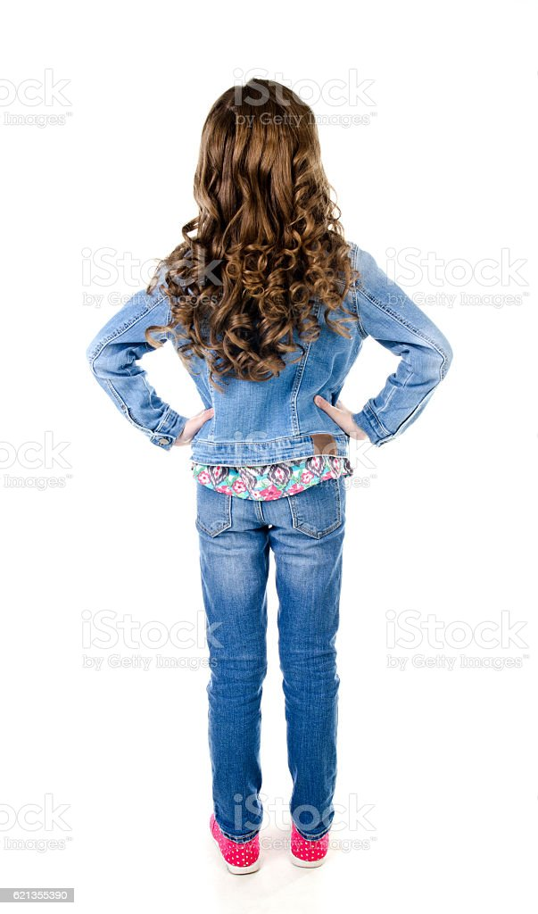 Portrait of adorable little girl in jeans standing back stock photo