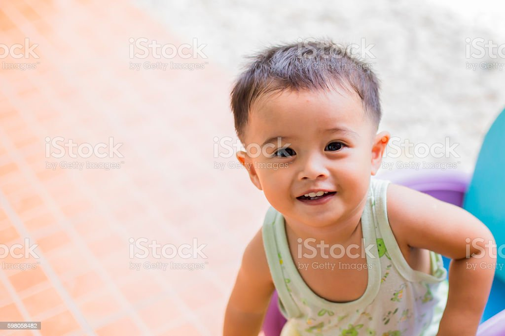 Portrait of adorable toddler boy looking into something and happy stock photo