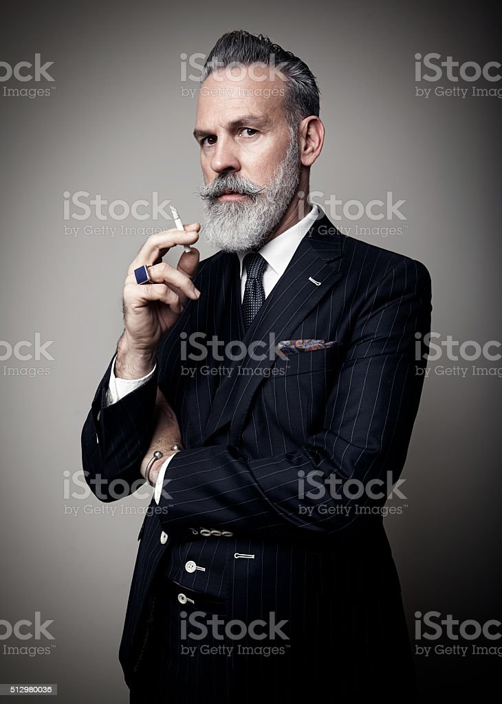 Portrait of adult businessman wearing trendy suit and holding cigarette stock photo