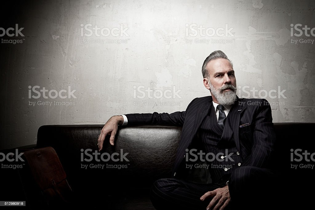 Portrait of adult businessman wearing trendy suit and sitting modern stock photo