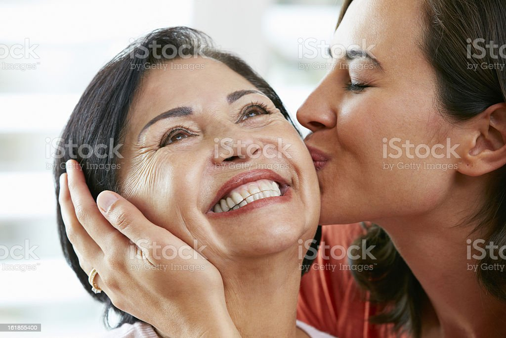 Portrait Of Adult Daughter Kissing Mother royalty-free stock photo