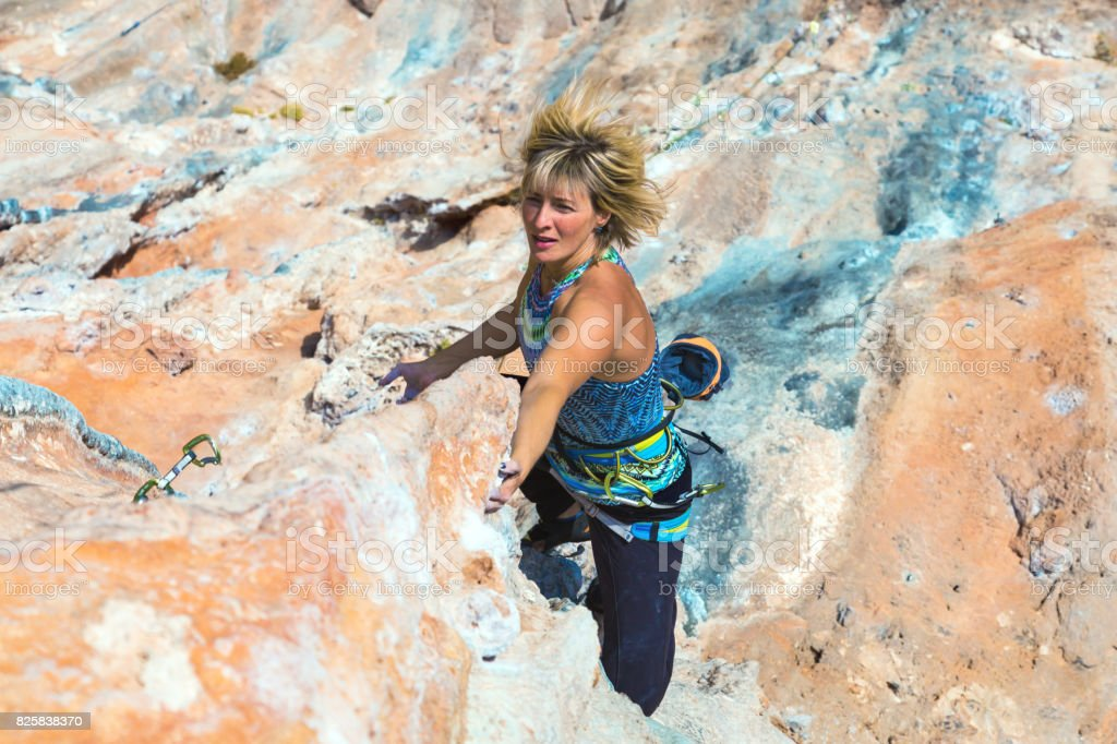 Portrait of adult Female Rock Climber moving up on difficult Wall stock photo