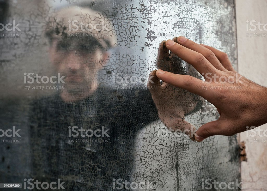Portrait Of Adult Man In Corroded Mirror stock photo