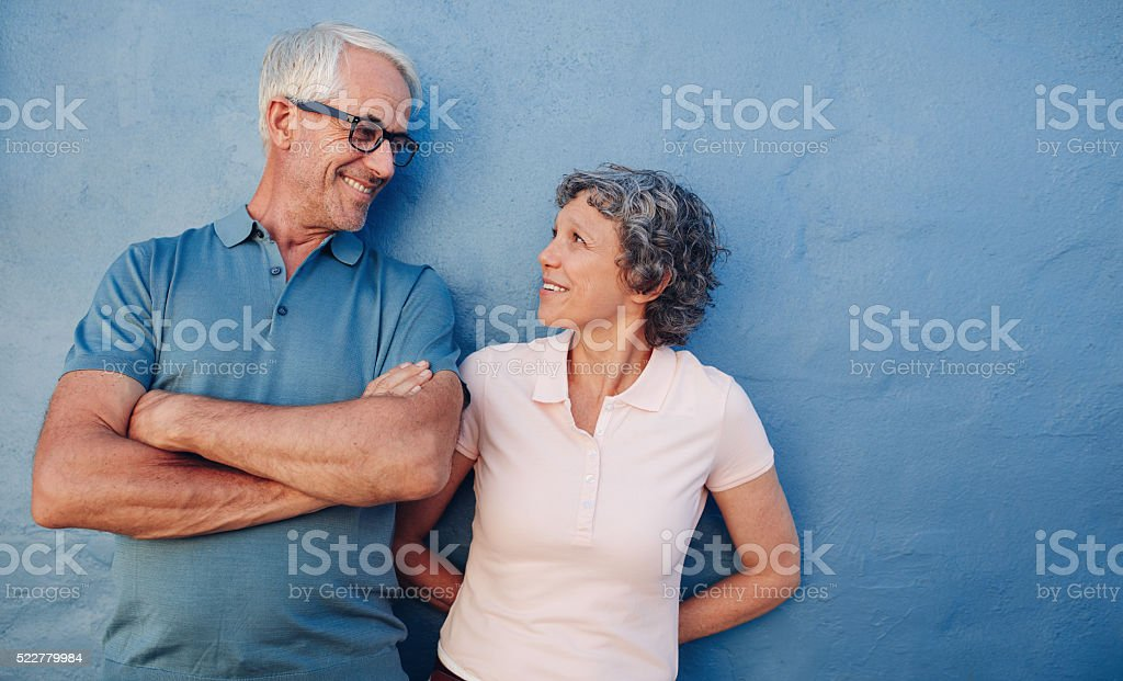 Portrait of affectionate mature couple against a blue wall stock photo
