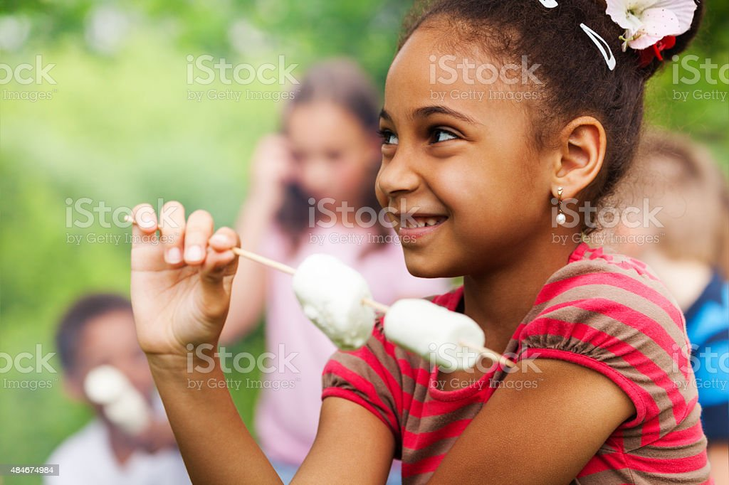 Portrait of African girl and marshmallow stick stock photo