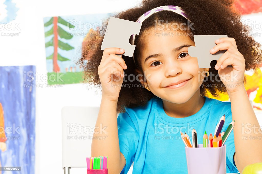 Portrait of African girl holding puzzle pieces stock photo