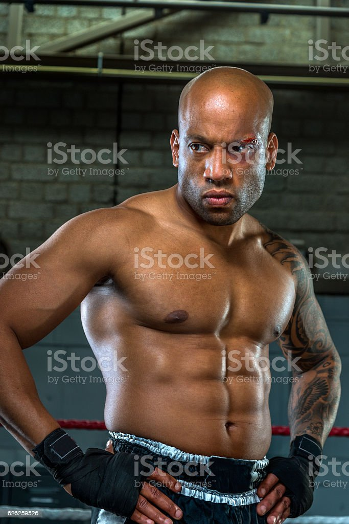 Portrait of aggressive and wounded boxer  in boxing gym stock photo