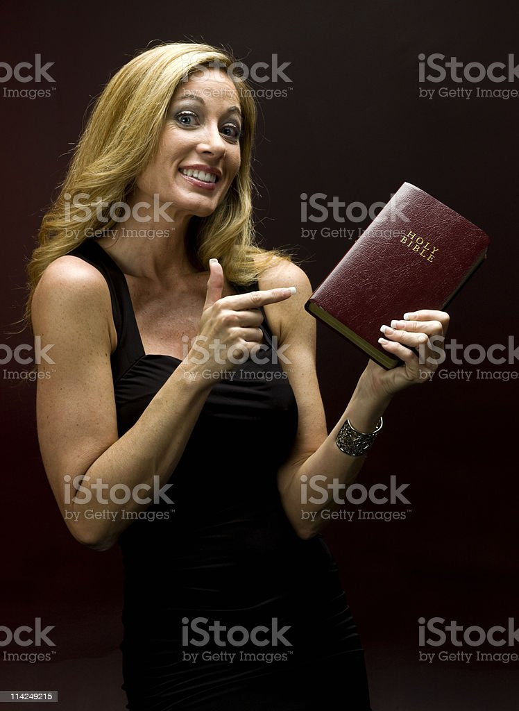 Portrait of an adult woman pointing at a bible royalty-free stock photo