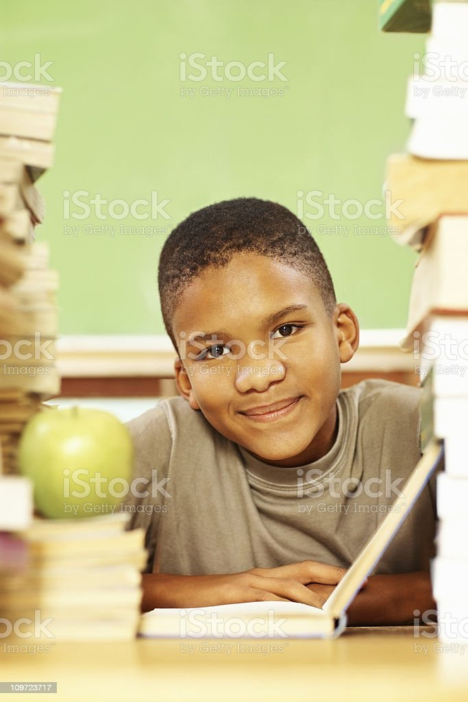 Portrait of an African American boy with book stack reading royalty-free stock photo