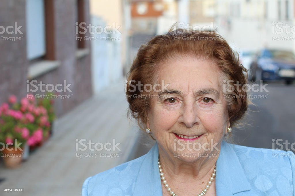 Portrait of an aged woman smiling outdoors stock photo