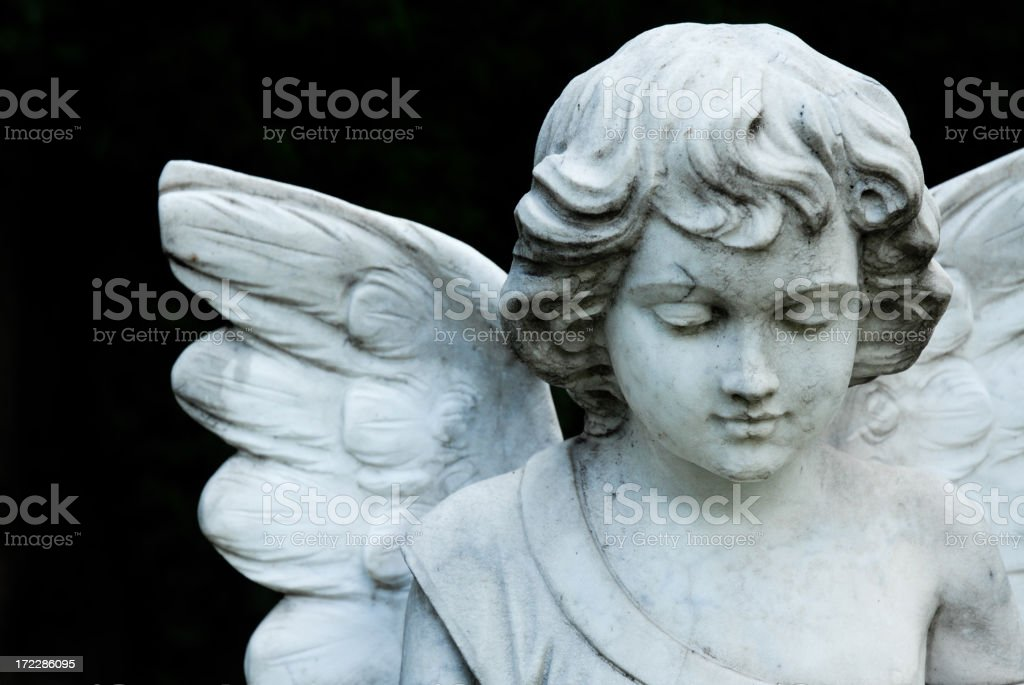 A portrait of an angel statue on a black background stock photo