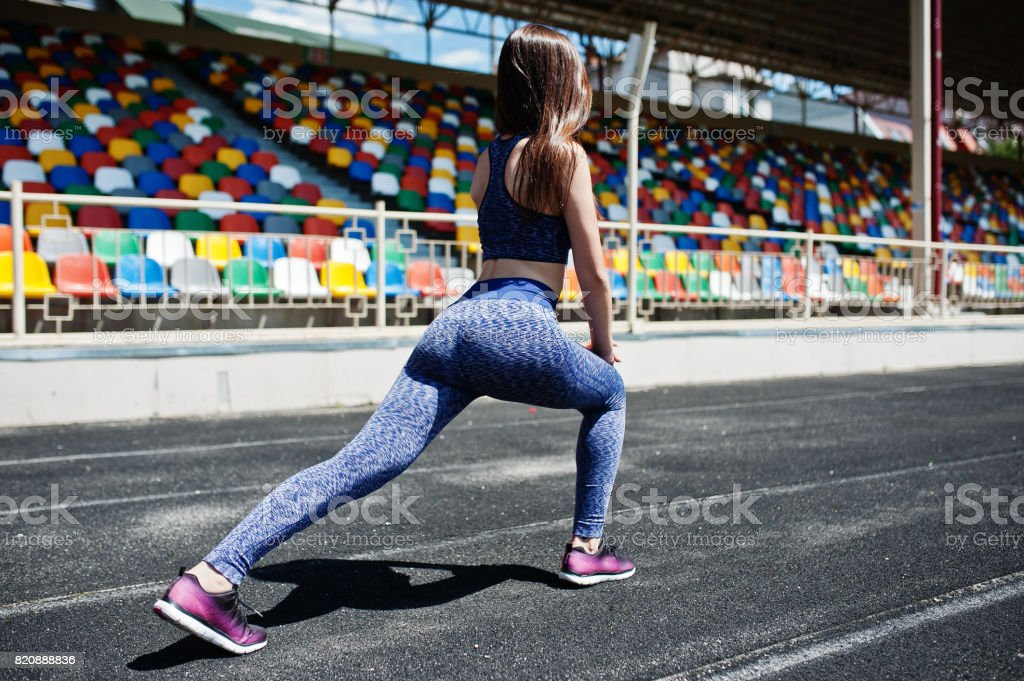 Portrait of an attractive fit woman doing exercises for her legs in the stadium. stock photo