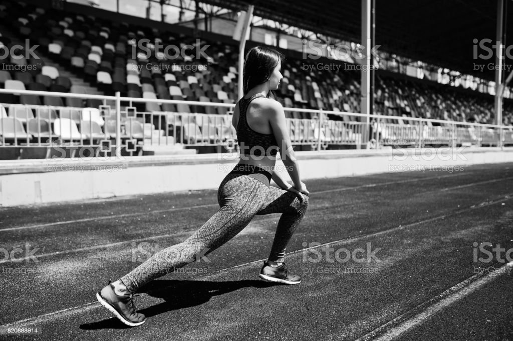 Portrait of an attractive fit woman doing exercises for her legs in the stadium. Black and white photo. stock photo
