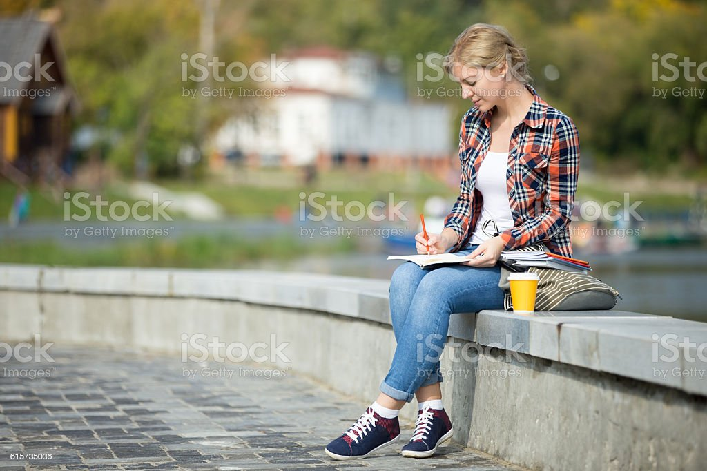 Portrait of an attractive student girl sitting at bridge writing stock photo