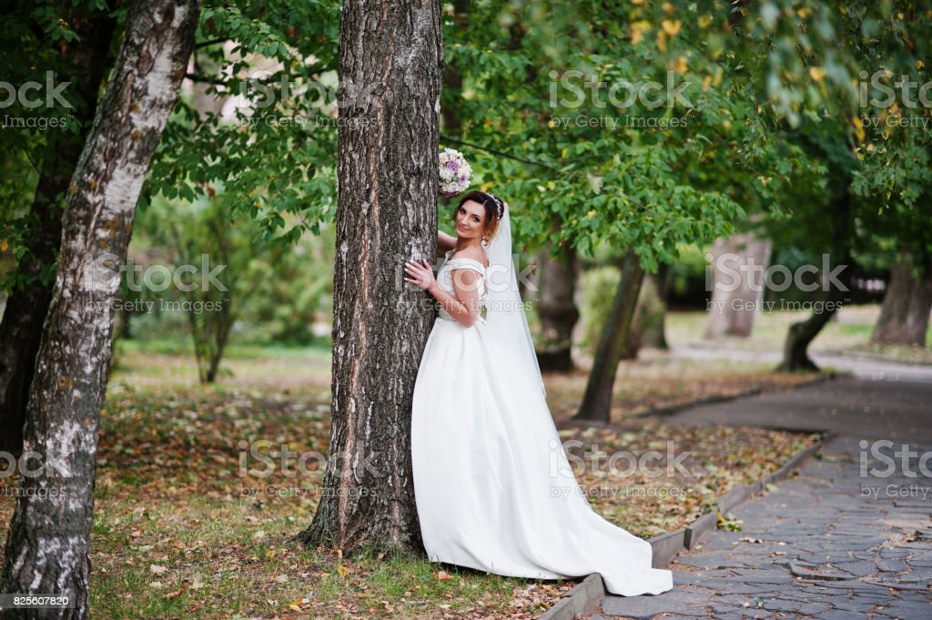 Portrait of an attractive young bride walking in the park on her own with a wedding bouquet in her hands. stock photo