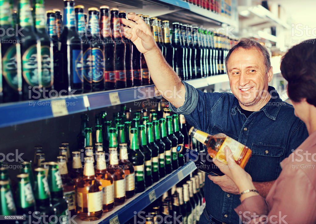Portrait of an elderly couple buying a beer stock photo