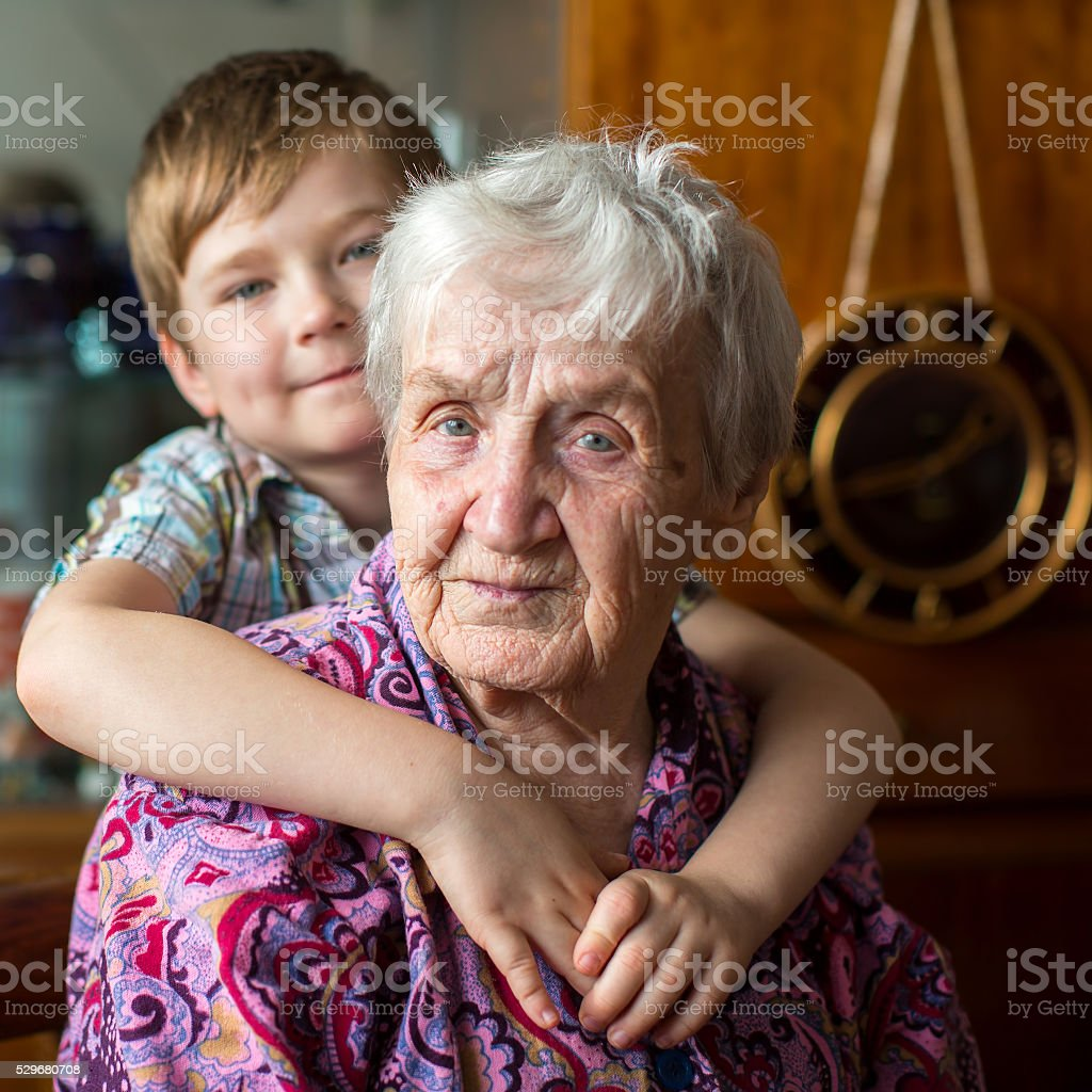 Portrait of an elderly woman, grandson at blurring in background. stock photo
