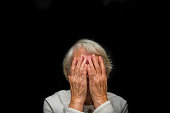 Portrait of an elderly woman with face closed by hands