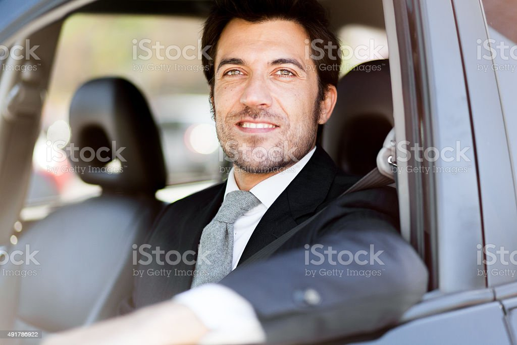 Portrait of an handsome smiling business man driving his car stock photo