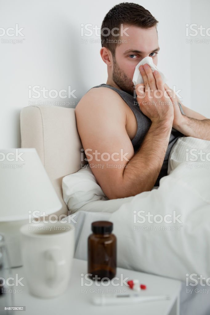 Portrait of an ill man blowing his nose stock photo
