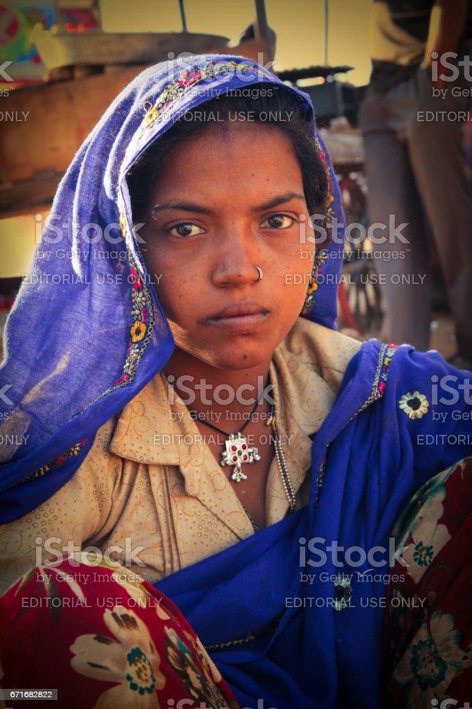 A portrait of An Indian Rajasthani rural woman looking at camera at Pushkar Camel Fair stock photo