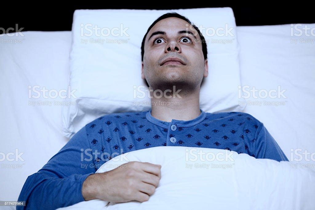 Portrait of an insomniac man trying to sleep stock photo
